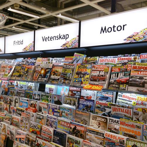 Tidningsställ i butik. LED-tejp används både i skyltarna ovanpå samt i hyllorna för att belysa tidningarna.